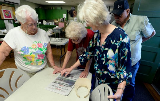 Elkmont residents look at a daily newspaper story Wednesday, Sept. 4, 2019, in Elkmont, Ala., about a shooting that happened in their community. A 14-year-old boy called 911 Monday night and later admitted to authorities he killed his parents and three younger siblings, including a 6-month-old baby, in Elkmont, near the Alabama-Tennessee border.