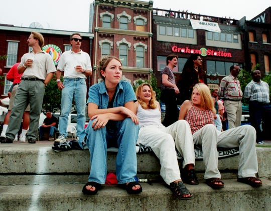 April Stotts, left, Katrina Mears, and Naomi Sheets enjoy the music of the Dancin' in the District on July 23, 1998, while adults behind them enjoy a beer. The three 18 year-olds drove up from McMinnville to attend the event for the first time because there are few things for teens to do in their hometown at night.