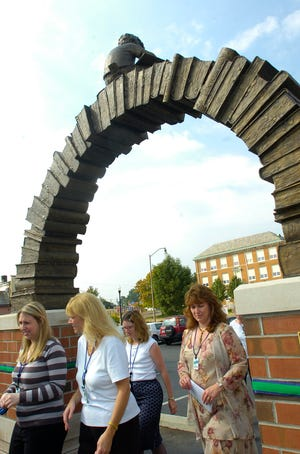 "Library personnel and visitors make their way beneath the new ""Learning Curve"" sculpture after its dedication in September 2007. (Morgan Wonorski, The Advocate)"