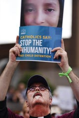 Deacon Tom Smith from St. John's in Newark, holds a picture of a girl who died after crossing the border, is seen during the rally to protest separation of immigrant families, in the middle of Broad and Court Streets in Newark on 09/04/19.