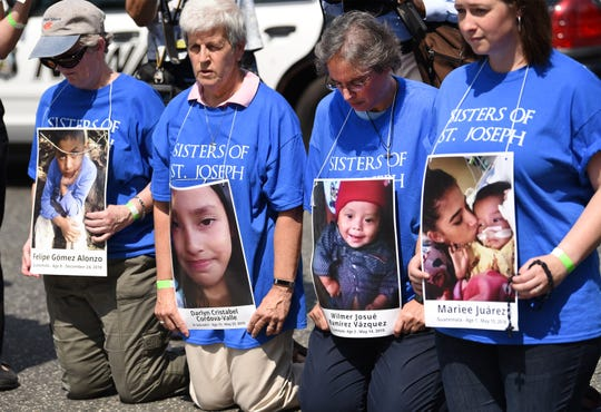 Protestors hold pictures of children who died after crossing the border, is seen during the rally to protest separation of immigrant families, in the middle of Broad and Court Streets in Newark on 09/04/19.