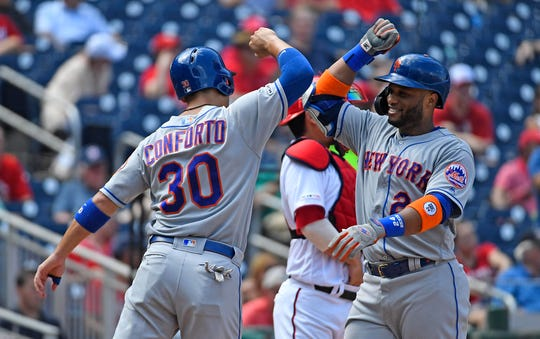 New York Mets second baseman Robinson Cano (24) celebrates with right fielder Michael Conforto (30) after hitting a two run home run against the Washington Nationals during the fourth inning at Nationals Park.