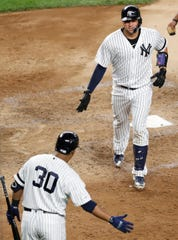 New York Yankees on-deck batter Edwin Encarnacion (30) greets Gary Sanchez after Sanchez hit his second home run of the night, in the sixth inning of the team's baseball game against the Texas Rangers, Tuesday, Sept. 3, 2019, in New York. (AP Photo/Kathy Willens)