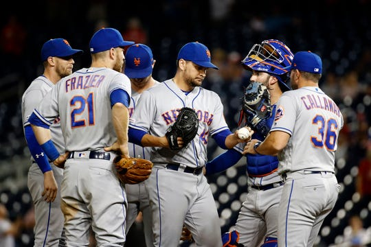 New York Mets relief pitcher Luis Avilan, center, is removed by manager Mickey Callaway during the ninth inning of the team's baseball game against the Washington Nationals, Tuesday, Sept. 3, 2019, in Washington. Washington scored seven runs in the ninth, and won 11-10.
