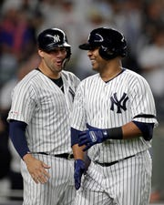 Edwin Encarnacion #30 of the New York Yankees is congratulated by Gary Sanchez #24 after hitting a two run home run against the Texas Rangers during the seventh inning at Yankee Stadium on September 3, 2019 in New York City.