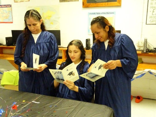 Otero County Prison Facility GED graduates figure out how to put on motarboard's for their graduation Aug. 29.