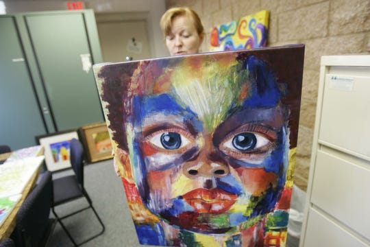 Erin Hourihan holds a painting prior to a fundraiser auction at Childhaven.