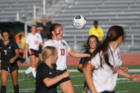 Aztec's Sierra Villanueva looks to gain control of the ball against Farmington during Tuesday's girls soccer match at Hutchison Stadium in Farmington.