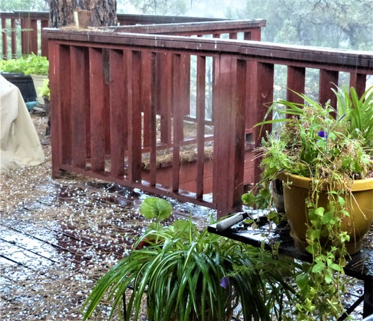 Hail from a summer thunderstorm in Ruidoso covers a deck, but left potted plants unharmed.