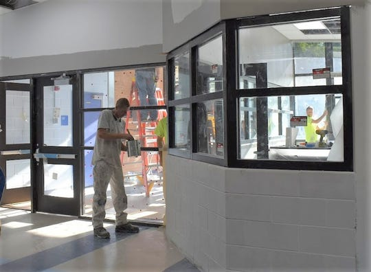 Workers put the finishing touches on Amerman's new secured entry way.