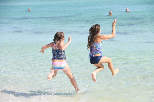 At left, Athena Miller, 8, and Janie Nowicki, 10, of Navarre, jump in the water at Navarre Beach on Wednesday, Sept. 4, 2019. Navarre Beach officials are stressing to the public that the water is safe for swimming after misinformation about water quality raised concerns earlier in the day.