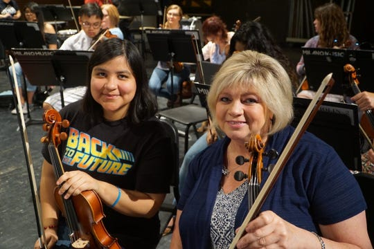 Diana Gomez (left) and Cindy Petty  practice before a concert with the MusicaNova orchestra.