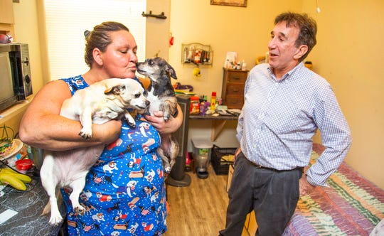 Robin Robinson, a resident at 209 W. Jackson, snuggles her dogs, Guera and Trevisa, right, as she speaks with resident services manager Fred Cohen in her apartment, Sept. 3, 2019. The facility, run by Arizona Housing, Inc., provides supportive housing to combat homelessness.