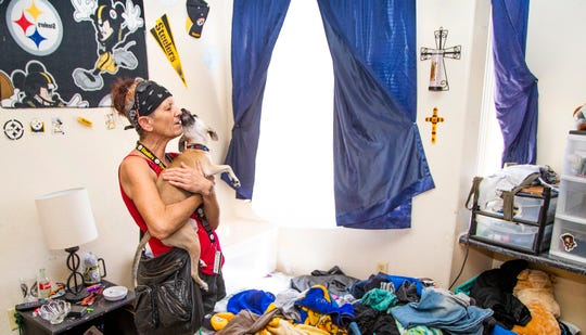 Lisa Klein, a resident at 209 W. Jackson, snuggles her dog, Chyna, in her apartment, Sept. 3, 2019. The facility, run by Arizona Housing, Inc., provides supportive housing to combat homelessness.