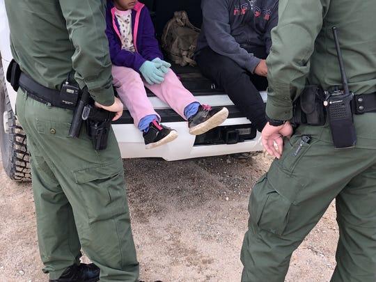 Fotografía del 22 de febrero donde aparecen dos agentes de la Patrulla Fronteriza mientras atienden a unos niños en un punto del área conocido como Quitobaquito, en la frontera de Arizona con México (EE.UU.).