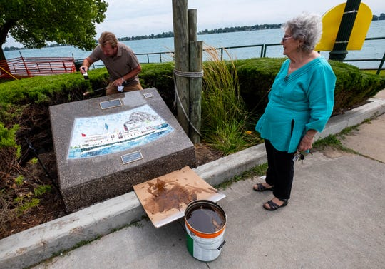 Heather Bokram, right, watches while Jeff Ward, owner of Ward Construction in Kimball, applies a sealant to the stone mount holding one of the tile mosaics created to be displayed in the city's parks Tuesday, Sept. 3, 2019, in Drake Park. Bokram created pastel paintings, which were turned into tile mosaics to be displayed throughout the city.