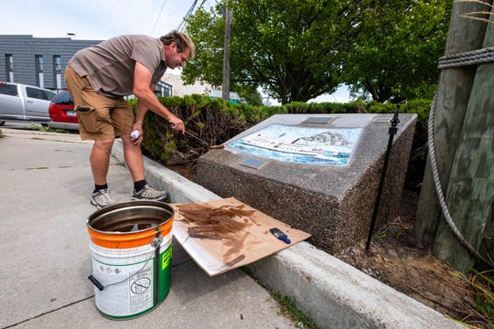 Jeff Ward, owner of Ward Construction in Kimball, applies a sealant to the stone mount holding one of the new tile mosaics in Marine City Tuesday, Sept. 3, 2019, in the city's Drake Park. The sealant, Ward said, is to help make the colors of the rocks show more.
