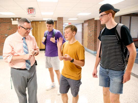 Red Hook High School principal Robert McKiernan speaks with seniors, from left, Luke Crittenden, Chris Donohue and Devon Flynn on the first day of school on September 4, 2019. The three seniors are involved in a mentoring program where they are paired with ninth graders to help them acclimate to high school.