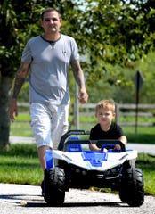 Rick Savastano follows his son Hunter, 4, as he rides his new battery powered car at Greenbriar Estates Wednesday, Sept. 4, 2019. The two have lived in the townhouse community for four years. The Conewago Board of Supervisors voted unanimously to approve the final plans for the construction of a community center in the development. Bill Kalina photo