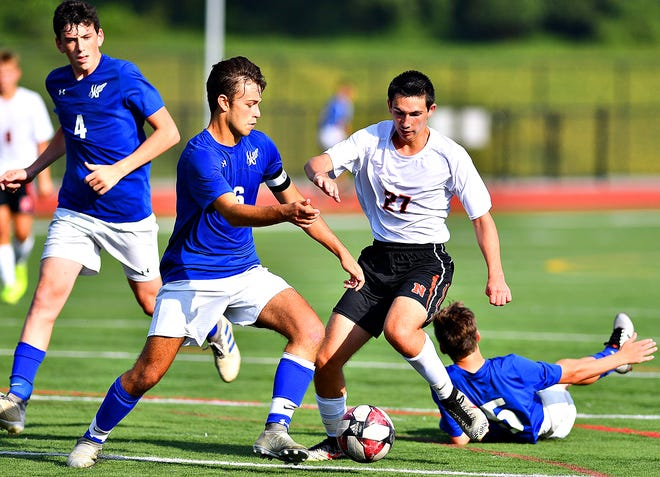 Spring Grove's Zach Speranzella, left, kicks the ball away from Northeastern's Ryan Draggoo during boys' soccer action in Papermakers Stadium at Spring Grove Area High School in Jackson Township, Wednesday, Sept. 4, 2019. Northeastern would win the game 3-1. Dawn J. Sagert photo