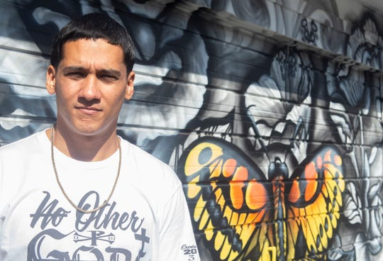"""Jonathan """"Skilz"""" Molina stands in front of his """"Rebirth"""" mural in the Royal Square District. It is one of 14 murals now within the downtown York neighborhood."""