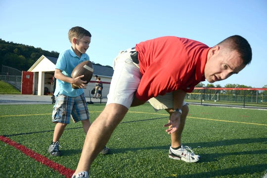 Announcer Kevin Lawrence hikes the ball to his son, 6-year-old Connor Lawrence before the football game at Susquehannock High School Friday, August 31, 2012.