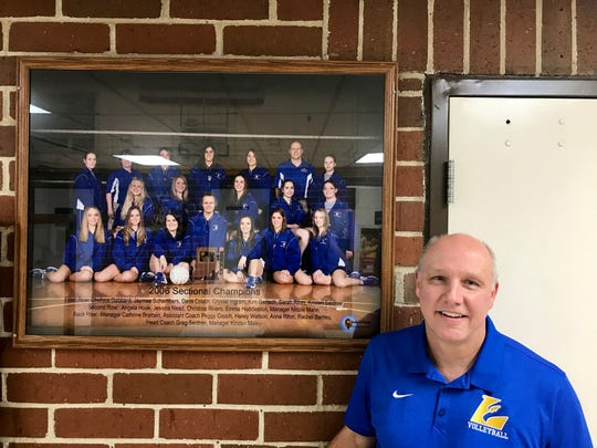 Cambridge City Lincoln volleyball head coach Greg Seidner next to a photo of his 2006 sectional championship team.