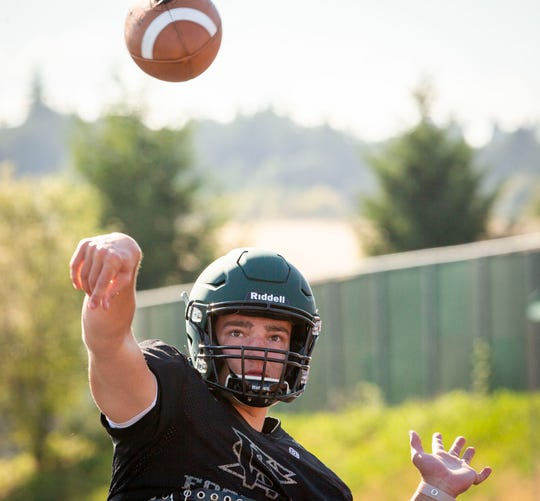West Salem High School football quarterback Jackson Lowery, center, practices with the team September 3, 2019, to prepare for their season-opening game against Lake Oswego.