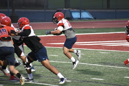 DSU running back Sei-J Lauago (center) carries the ball during practice.