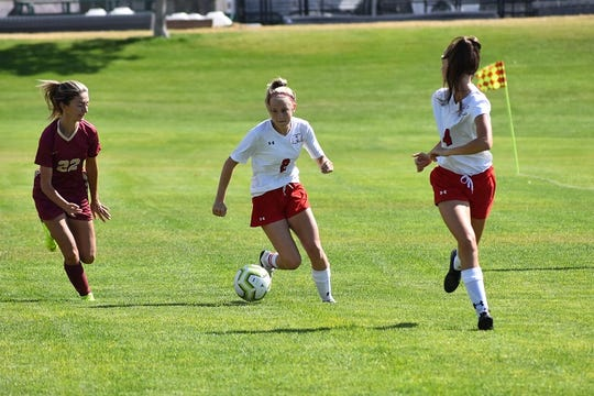 Hurricane forward Madelyn Hatch plays the ball ahead during Hurricane's match against Cedar. Hatch scored two goals against the Reds.
