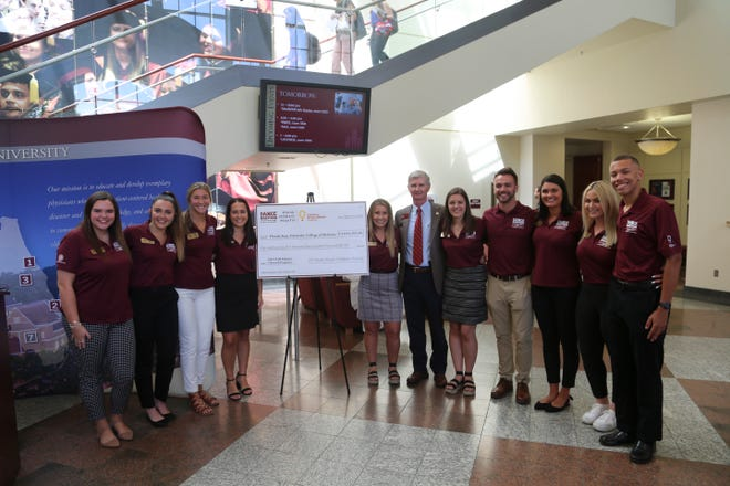 FSU College of Medicine Dean John P. Fogarty, sixth from left, stands with Dance Marathon at FSU executive committee members during a check presentation on Sept. 4, 2019.