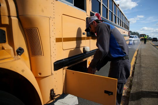 A mechanic works to turn off the bus to stop the smoke that continued to pour out of the Leon County School bus. The bus was parked on Capital Circle Northeast and children were safely removed and transferred to a new bus.