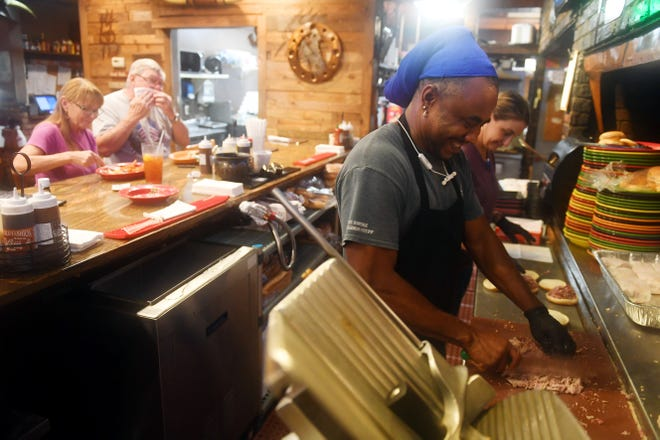 """Mike Doasca (right) prepares a chop pork plate on Wednesday, Sept. 4, 2019, at Wilke's 14 Bones Barbecue in Vero Beach as residents take advantage of being out of the house after Hurricane Dorian passed by the Treasure Coast. """"We were open on Tuesday as well from about 10:30 a.m. to 2:30 p.m.,"""" said general manager Brian Mock. """"Everyone was pretty grateful we were open."""""""