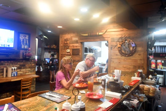 """Jan Drygulski and Bob Lund, both of Vero Beach, enjoy a barbecue lunch at Wilke's 14 Bones Barbecue in Vero Beach on Wednesday, Sept. 4, 2019, after Hurricane Dorian passed by the Treasure Coast. """"You kind of start to to go stir crazy from being in the house for so long,"""" Lund said. """"We're finally able to get out and run some errands."""""""