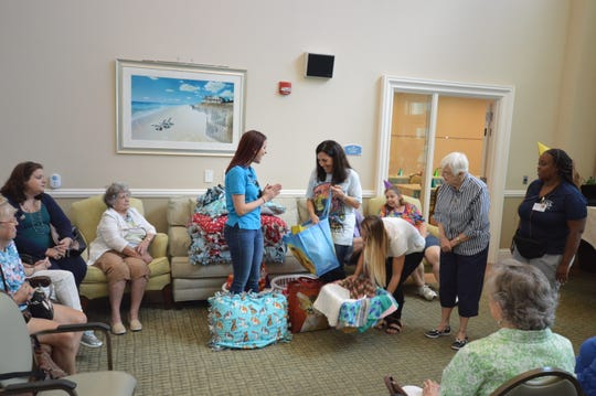 Memory Cafe Facilitator Nancy Firpo Ginden presents Jessie Clifford of the Humane Society of the Treasure Coast with handmade gifts, treats and toys for their shelter animals at at Grand Oaks of Jensen Beach.