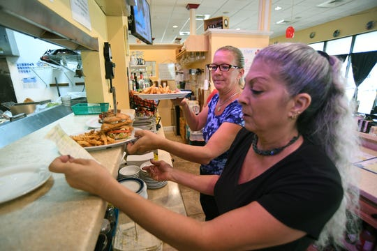 "Lauren Wilkerson (front), manager of Rick's Diner, at the Coco Vista shopping plaza in Port St. Lucie, and server Cheryl Wise, take care of the lunch orders for their customers after reopening the diner on Wednesday, Sept. 4, 2019, after Hurricane Dorian passed the Treasure Coast of Florida. ""Busy, very busy, this is our first day opening after the storm,"" Wilkerson said. ""We did not have any damage other than the poor squirrel falling out of the tree on Saturday."""