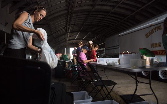 "Krista Singleton (left), of Palm City, with the non-profit Village Club & Preserve in Palm City, helps Karen Vaughn (center), of Stuart, with Operation 300, as they begin the non-profit's Bahamas relief collection efforts, following the devastation left by Hurricane Dorian, in Hangar 3 at Witham Field on Wednesday , Sept. 4, 2019, in Martin County. ""We're just big fans of Operation 300, we know they're a trustworthy organization,"" Singleton said."