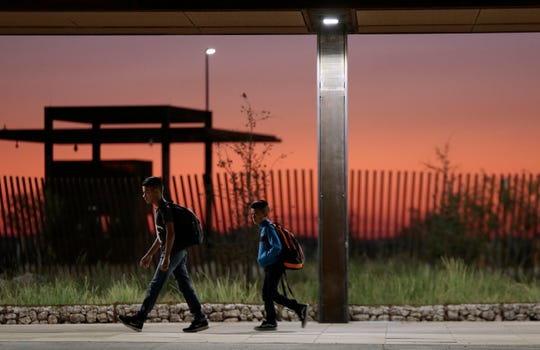 Columbus Elementary School students walk alone across the the new port of entry between Columbus and Palomas early Wednesday morning as the sun rises behind them.