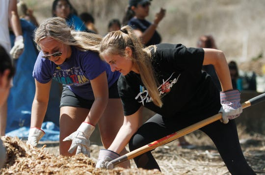 """California Lutheran University student Alexandra Infante, left, works with classmate Olivia Larson to transfer mulch to tarps for transport Tuesday at the Ventura Botanical Gardens. Students of the Thousand Oaks university were a part of """"You Got Served,"""" a program that partners with the city of Ventura."""