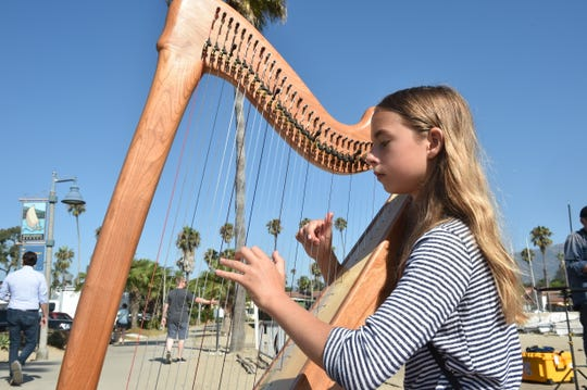CJ Andelman, of Santa Barbara, plays a harp Sept. 4, 2019, at a makeshift memorial at Santa Barbara Harbor for victims of the deadly fire aboard the Conception near Santa Cruz Island. Those who knew victims and others moved to pay tribute have gravitated toward the harbor.