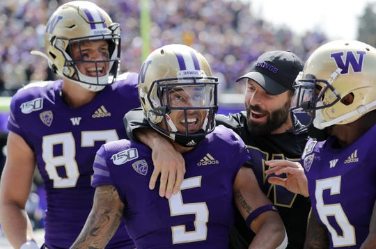 Washington's Andre Baccellia (5) is congratulated after scoring a touchdown against Eastern Washington in last Saturday's game. The Westlake High graduate finished with five catches for 86 yards.