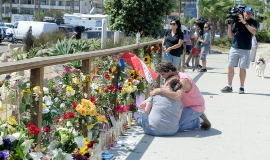 A woman who identified herself as the mother of Allie Kurtz is comforted at a memorial for victims of the Santa Cruz Island boat fire Tuesday, Sept. 3, 2019, in Santa Barbara, California. Allie Kurtz is believed to be among the victims.