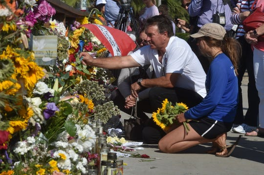 From right, Addison Martinez, Bill Krebs and Cassidy Krebs pay their respects Wednesday at a makeshift memorial at Santa Barbara Harbor to those lost in the fire aboard the diving boat Conception near Santa Cruz Island.