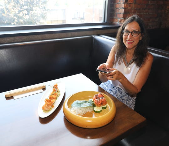 Food & Dining reporter Jeanne Muchnick snaps a photo of the Spicy Tuna Gyoza and the Crispy Rice, at ISO Japanese Cuisine in Yonkers, Aug. 1, 2019.
