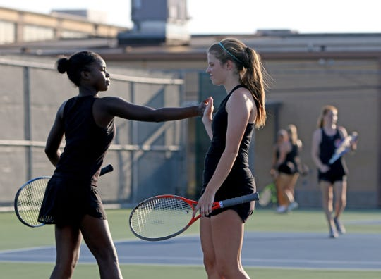 Rider's Skyla Preston, left, and Heather Hughes encourage each other after a game in a doubles match against Denton Braswell Tuesday, Sept. 3, 2019, at Rider.