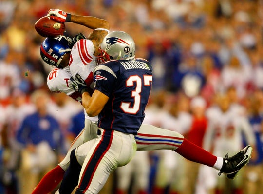 New York Giants receiver David Tyree catches a pass while in the clutches of New England Patriots safety Rodney Harrison  during the fourth quarter of the Super Bowl XLII football game in Glendale, Ariz. on Feb. 3, 2008.