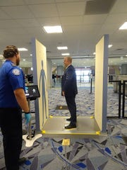 Greg McIntyre, the TSA's transportation security manager in Las Vegas, demonstrates a new body scanner, an an enhanced advanced imaging technology machine,  being tested at a new checkpoint in the basement of the airport.