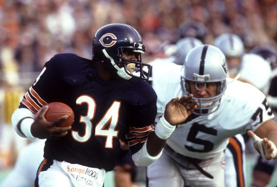 Chicago Bears running back Walter Payton is chased by Los Angeles Raiders defensive end Howie Long at Soldier Field on Nov. 4, 1984 in Chicago. The Bears defeated the Raiders 17-6.