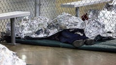 MCALLEN, TX – A detained immigrant sleeps under mylar blankets inside a holding cell at the Border Patrol's processing center in McAllen, Texas on Aug. 12, 2019.