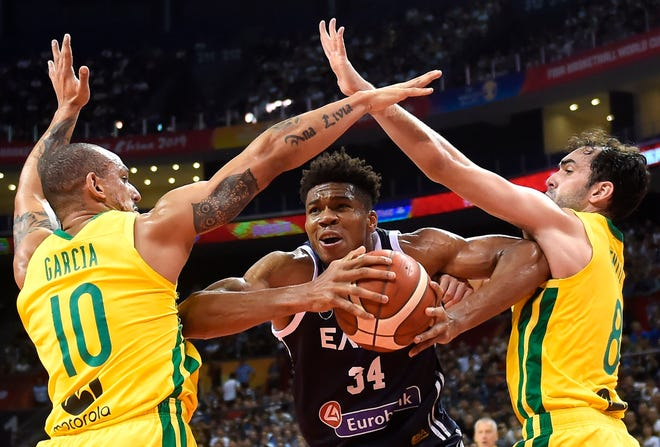 Greece's Giannis Antetokounmpo, center, tries to handle the ball through Brazil's Alex Garcia, left, and Brazil's Vitor Benite during the Basketball World Cup Group F game between Brazil and Greece in Nanjing, China.